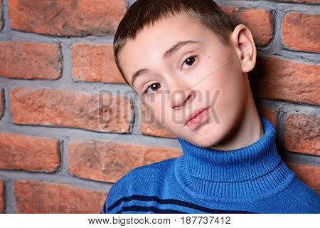 Portrait of a nine year old boy leaning against the brick wall.