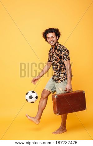 Image of cheerful young handsome african man standing and holding suitcase and football isolated over yellow background. Looking at camera.