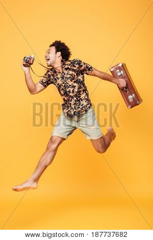 Full length portrait of a happy african man in summer clothes jumping and taking photo with retro camera isolated over yellow background