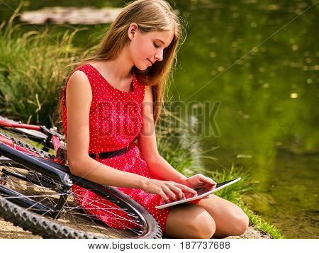 Bikes cycling girl wearing red polka dots dress recreation near bicycle into park. Children watch tablet pc in ecotourism. Femle went into social network in campaign.