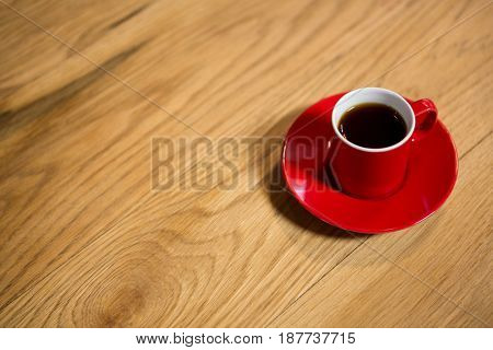 Close-up of red cup and saucer on table in cafeteria