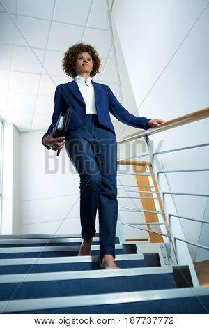 Businesswoman with diary climbing down the stairs at conference centre