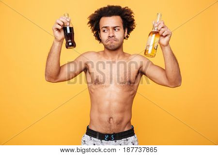 Portrait of a frustrated shirtless african man choosing a drink over yellow background