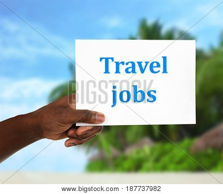 Concept of tourism and work. African-American man holding paper with text TRAVEL JOBS and blurred landscape on background