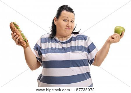 Indecisive overweight woman with a sandwich and an apple isolated on white background