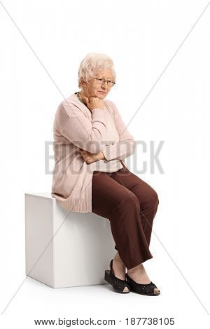 Sad mature woman sitting on a cube isolated on white background