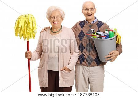Seniors with a mop and a bucket filled with cleaning products looking at the camera and smiling isolated on white background
