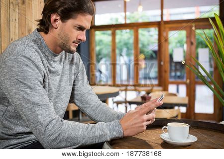 Handsome young man using smartphone at table in coffee shop