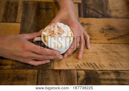 Close-up of man hands holding coffee cup at table in cafeteria