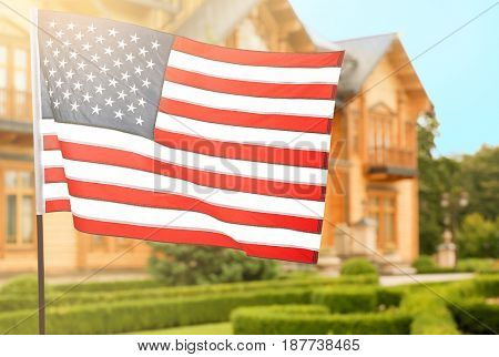 Waving USA flag and blurred house on background