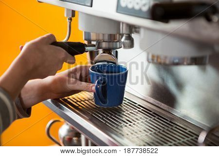 Close-up of female barista preparing coffee with machine in cafeteria