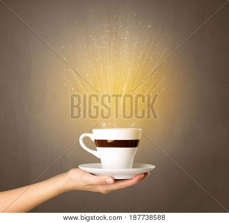 Young female hand holding coffee cup with a beam of light rising out of it