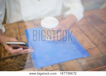 Midsection of woman holding coffee cup and mobile phone seen through cafe window