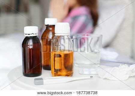 Medicines, electronic thermometer and tissue on table against blurred background