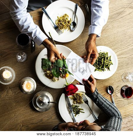 Man giving a rose and propose for the lady at dinner