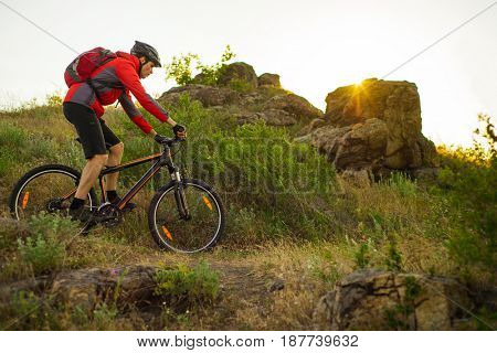Cyclist in Red Jacket Riding the Mountain Bike on the Beautiful Spring Rocky Trail at Sunset. Adventure and Extreme Sport Concept