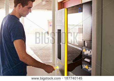 Young Man Paying For Car Parking At Machine
