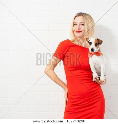 Beautiful happy woman in red dress with dog. Female against a white wall