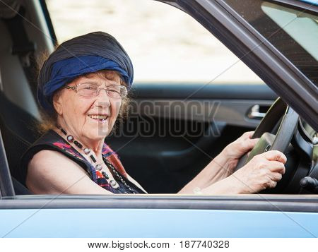 Happy granny at car. Old woman driving. Seniors