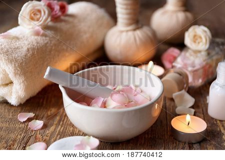 Beautiful spa composition with rose petals in bowl on wooden table