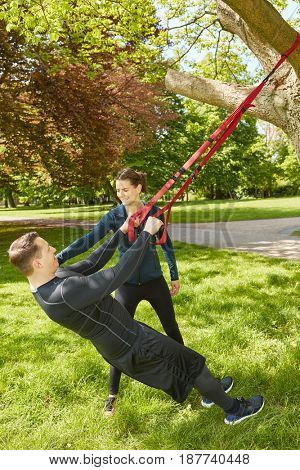 Man sling and suspension training using tree at the park