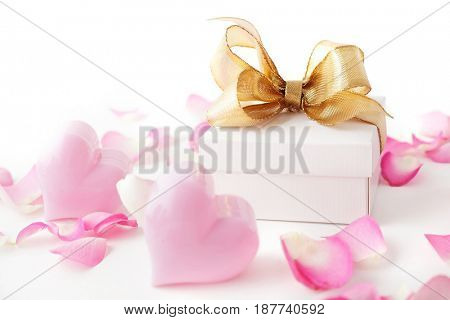 gift box tied with a gold ribbon bow, rose petals and pink hearts on white background