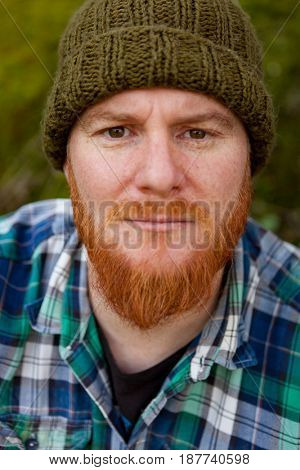 Portrait of a red haired man thinking in th forest