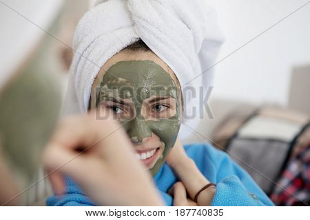 Mom and her daughter chilling in the bedroom and making clay facial mask.