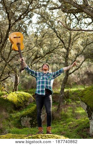 Happy hipster man with red beard and a guitar in the field