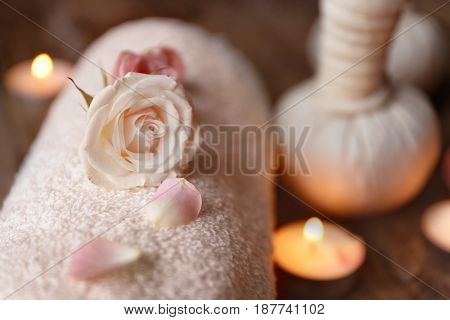 Beautiful rose on rolled towel in spa salon, closeup