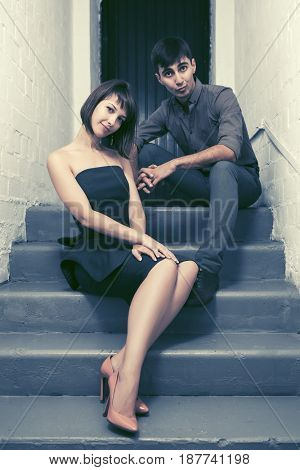 Happy young couple sitting on the steps at apartment