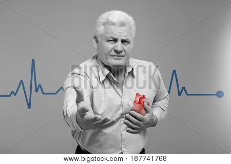 Heart attack concept. Senior man suffering from chest pain on gray background