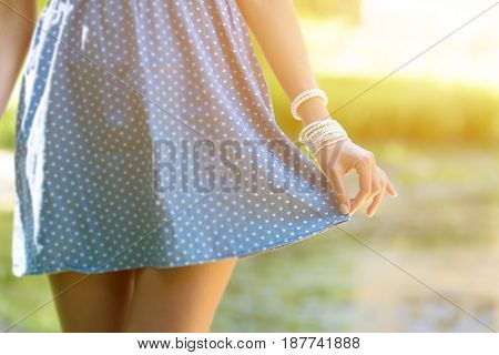Beautiful young woman wear in a short dress. Girl holding hand edge of the skirt , close-up on green park background