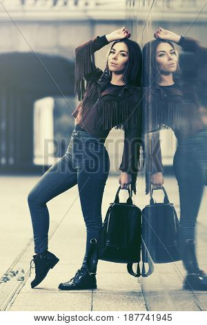 Happy young woman standing at the wall in city street. Stylish fashion model in leather fringe suede jacket and blue jeans