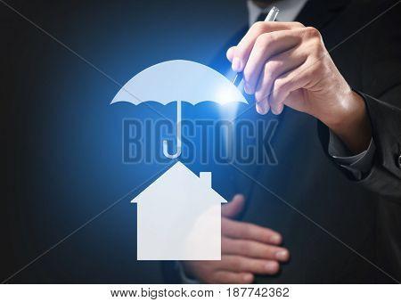 Insurance concept. Businessman drawing umbrella over house, closeup