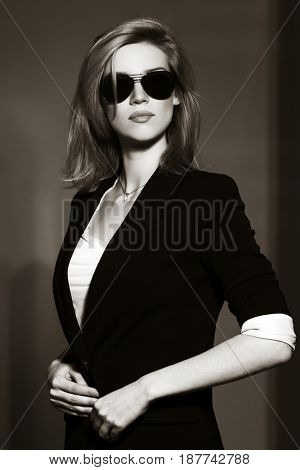 Young business woman walking in city street. Stylish fashion model in sunglasses