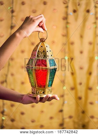 Close up of hands of an young girl holding a beautiful traditional Egyptian Ramadan lantern. This 'Fanous' is widely used to decorate by muslims during Holy month of Ramadan.