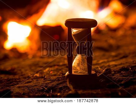 Hourglass in darkness against hot fire