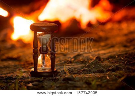 vintage hourglass in darkness against hot flame