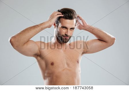 Portrait of a charming naked bearded man posing and touching his hair isolated over white background