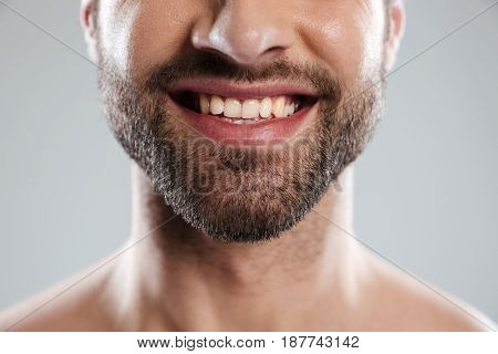 Cropped image of a laughing mans face with naked shoulders isolated over white background