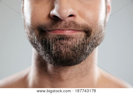 Cropped image of a doubtful bearded mans face isolated over white background