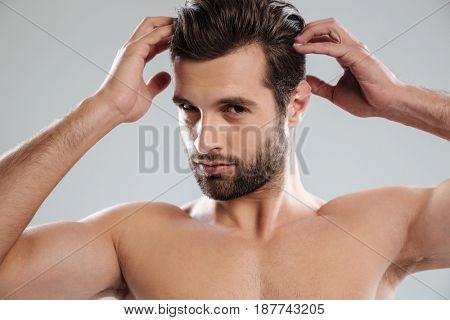 Close up portrait of a charming naked bearded man looking at camera and touching his hair isolated over white background