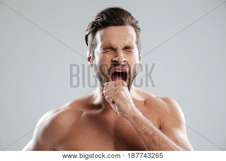 Portrait of a handsome bored beraded man with naked shoulders yawning isolated over white background