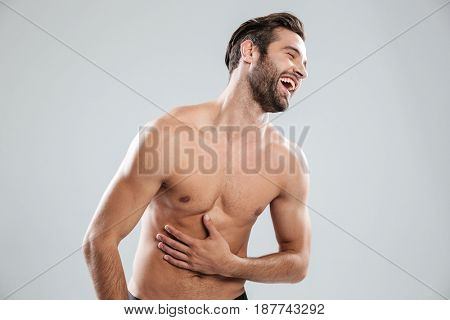 Portrait of a handsome bearded shirtless man doubling up with laughter isolated over white background