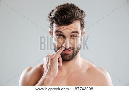 Portrait of a young bearded naked man picking his nose isolated over white background