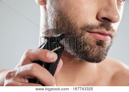 Cropped image of a young bearded man using electric shaver isolated over white background