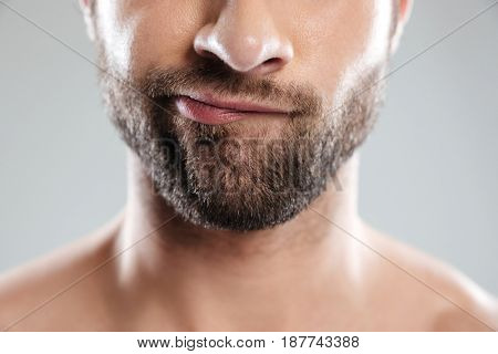 Cropped image of a thoughtful bearded mans face isolated over white background