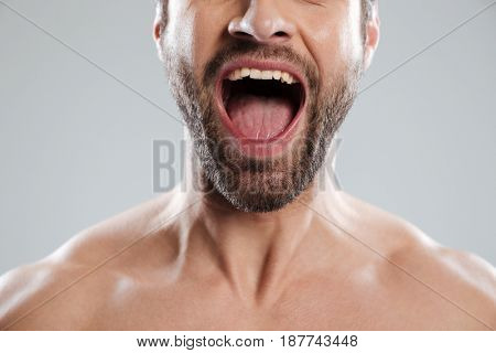 Cropped image of an excited mans half face with naked shoulders and open mouth isolated over white background