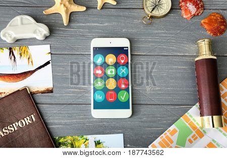 Modern technology and tourism, travel apps concept. Smartphone on wooden background